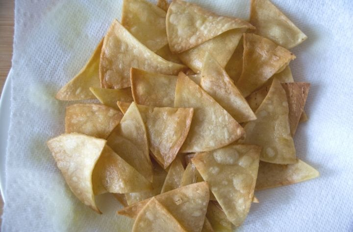 fried tortilla chips draining on paper towels