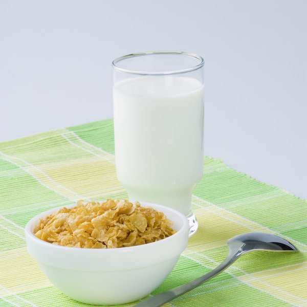 glass of milk with bowl of cereal and spoon
