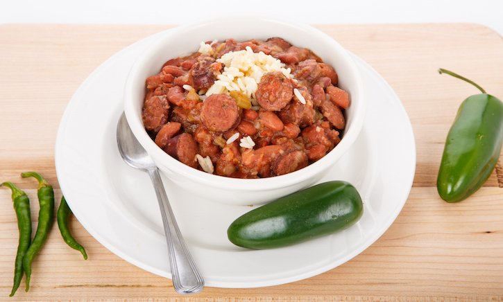 A bowl of red beans and rice with sausage and green jalapeno peppers