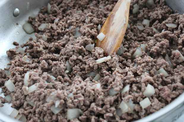 browning ground beef and onion in frying pan and stirring with wooden spoon