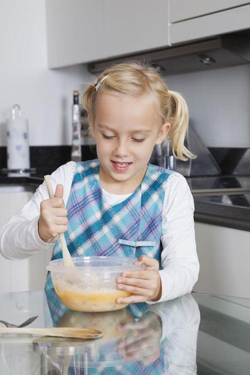 kid stirring ingredients in bowl