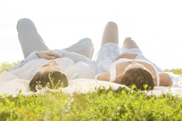 Couple on Romantic Picnic Lying on Blanket on Grass