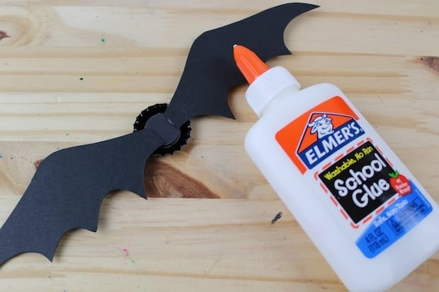 glue bat wings to bottle cap