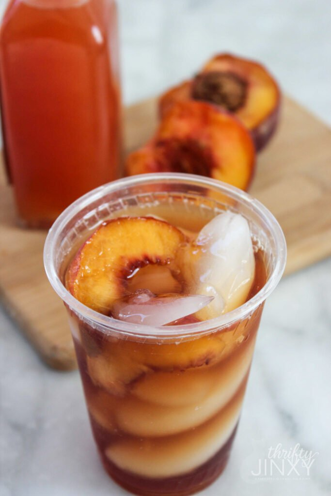Copycat Sonic Peach Iced Tea in plastic cup with fresh peaches on cutting board in background