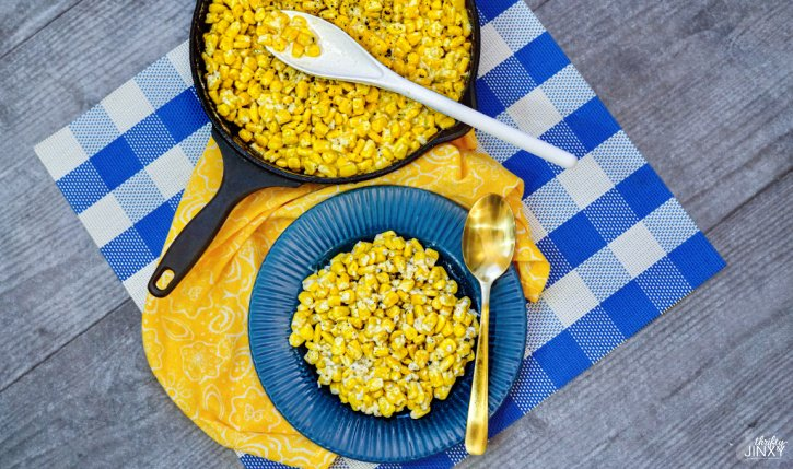 Creamed corn in a cast iron skillet with a serving on a blue plate