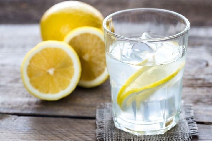 Glass of water with lemon slices for lemon water detox