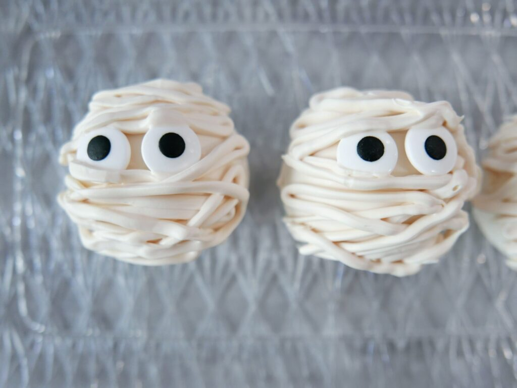 decorating candy mummies with edible eyes and strands of white chocolate