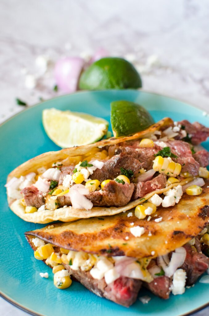 street tacos on plate with slice of lime
